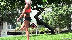 Busty blonde is working out and stretching in the great outdoors