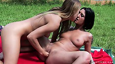 In the garden, a sexy blonde fucks a wild brunette with a strap-on dildo