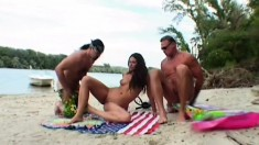 Exciting brunette with lovely big tits has two studs fucking her holes on the beach