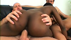 Seductive black girl with a perky booty has a pair of white studs fucking her holes