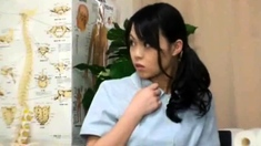 An Asian teen in a schoolgirls uniform is sitting on the