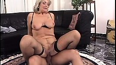 Mature blonde in fishnets moans while riding a throbbing cum gun